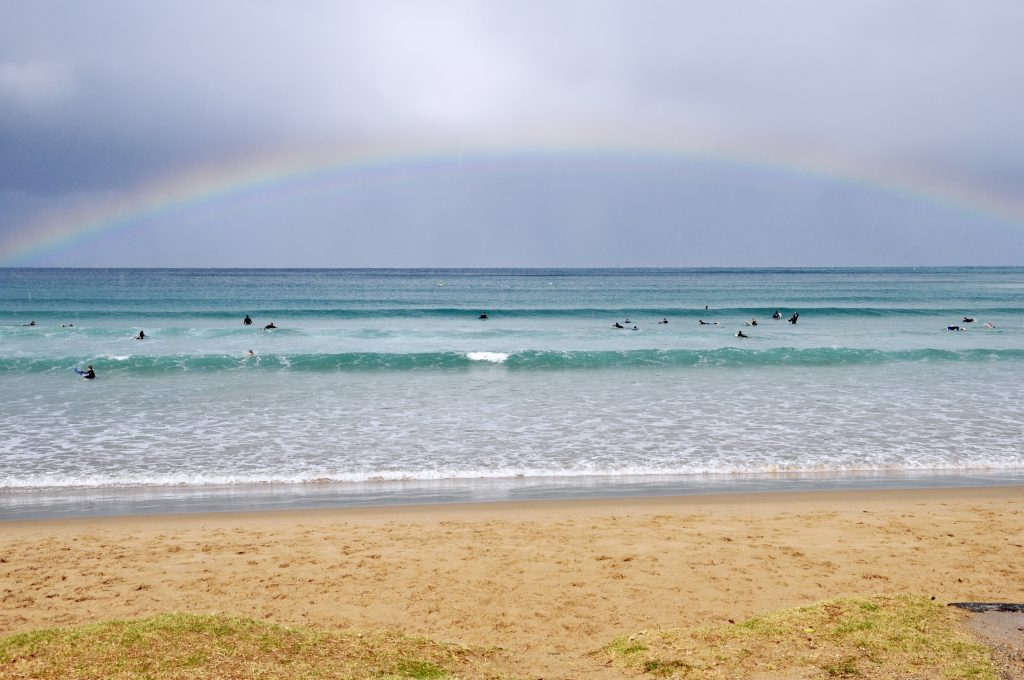 Lorne beach with rainbow and surfers on Great Ocean Road